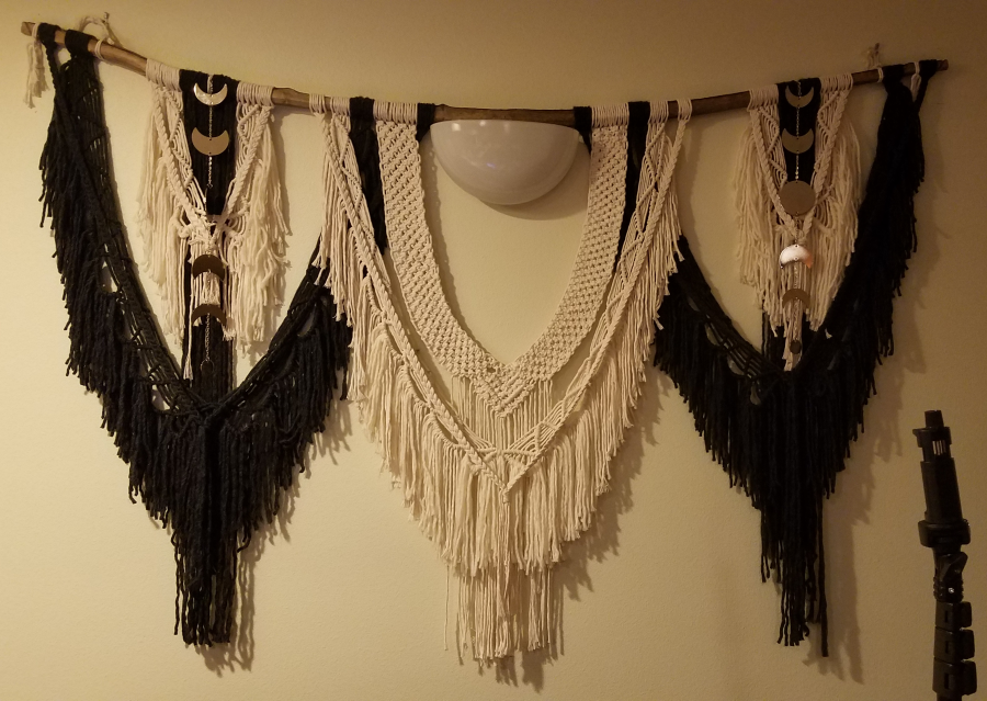 black and cream macrame wall hanging surrounding wall sconce with moon phase metal attachments